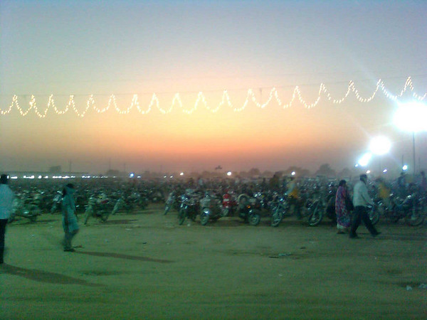 Photo of a huge motorcycle parking lot, lit up with carnival lights